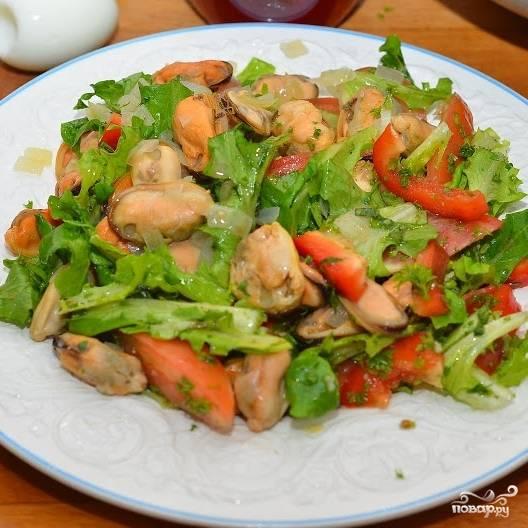 Выкладываем на тарелку порцию салата, поверх салата выкладываем мидии.