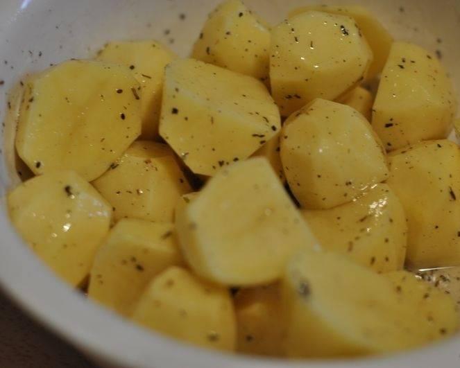 3. Очистить картофель, нарезать небольшими кубиками и выложить сперва в глубокую мисочку. Добавить по вкусу соль и специи, как следует перемешать. Взбрызнуть оливковым маслом.