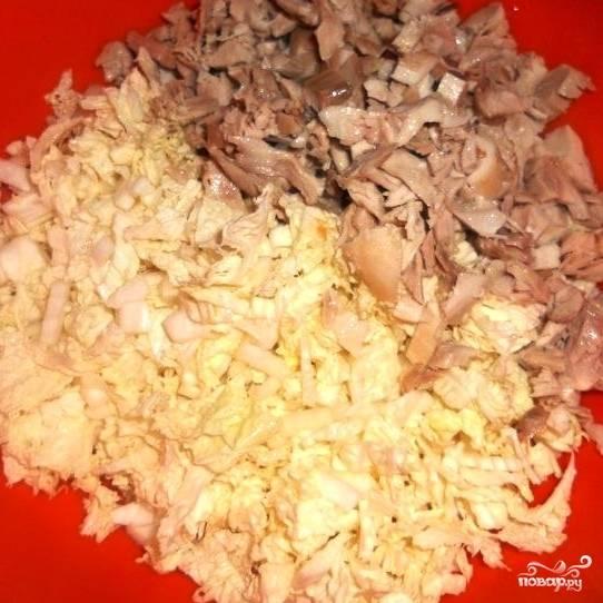 К нашинкованной капусте добавляем некрупные кусочки курицы.