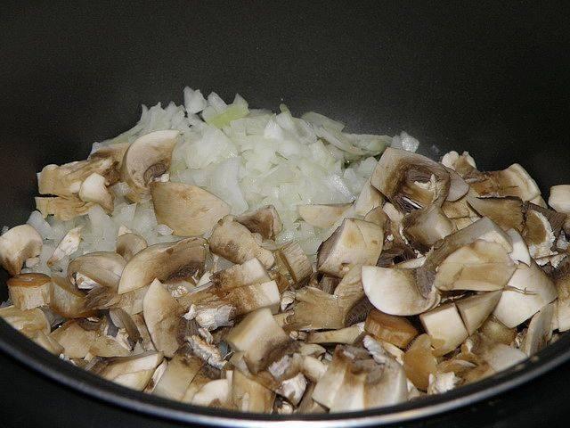 Лук и грибы нарежьте кубиками и добавьте в чашу мультиварки.