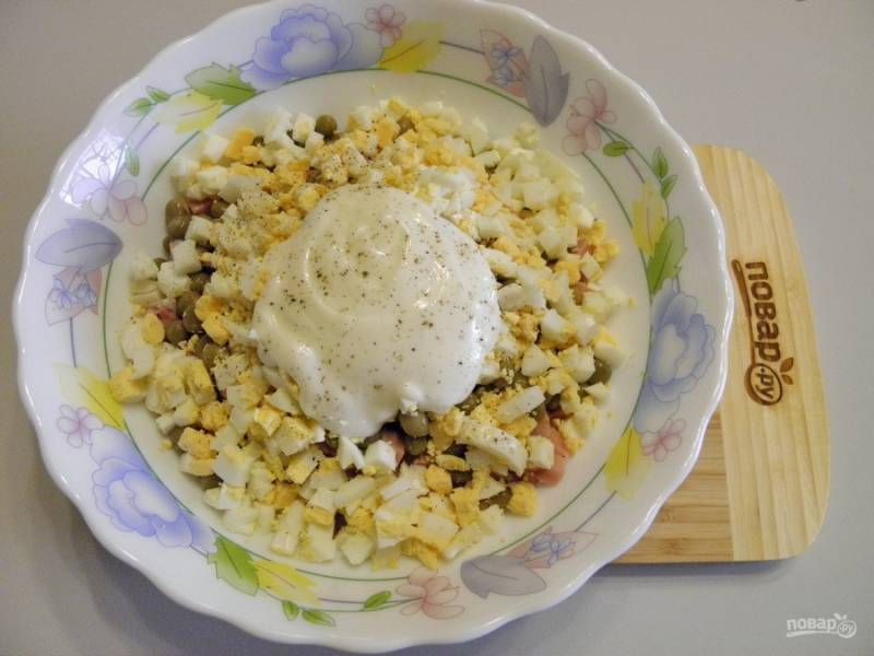 Отделите три белка для украшения салата, остальные яйца порежьте кубиками. Заправьте салат майонезом, посолите, поперчите. Перемешайте.