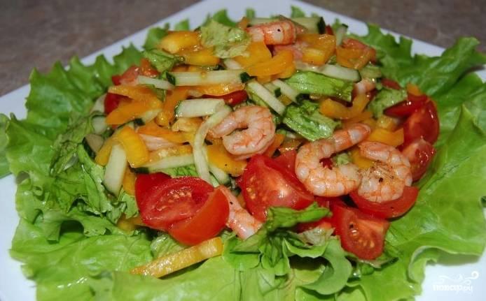 Поверх салатных листьев на тарелку положите остальные овощи. На овощи выложите креветки. Приготовьте заливку, смешав соевый соус и оливковое масло. Сбрызните заливкой салат — и он готов.