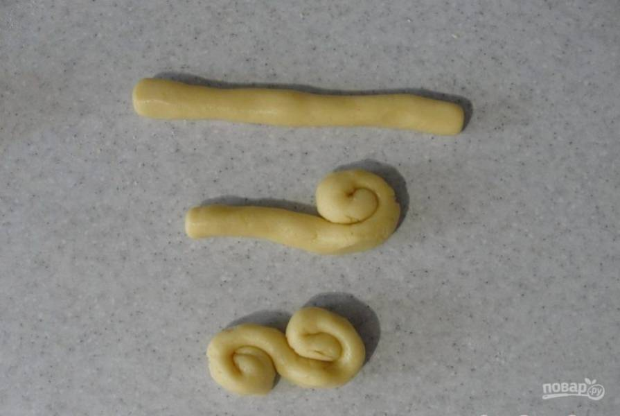 Сделайте печенье любой формы. Например, скрутите жгуты, а потом сверните их в завитки.