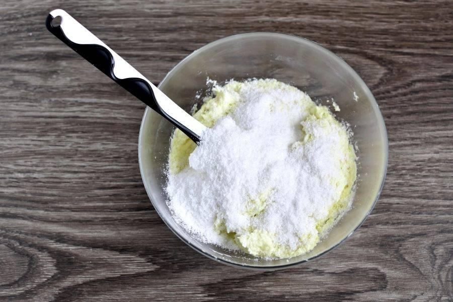 Всыпьте в крем кокосовую стружку и перемешайте лопаткой.