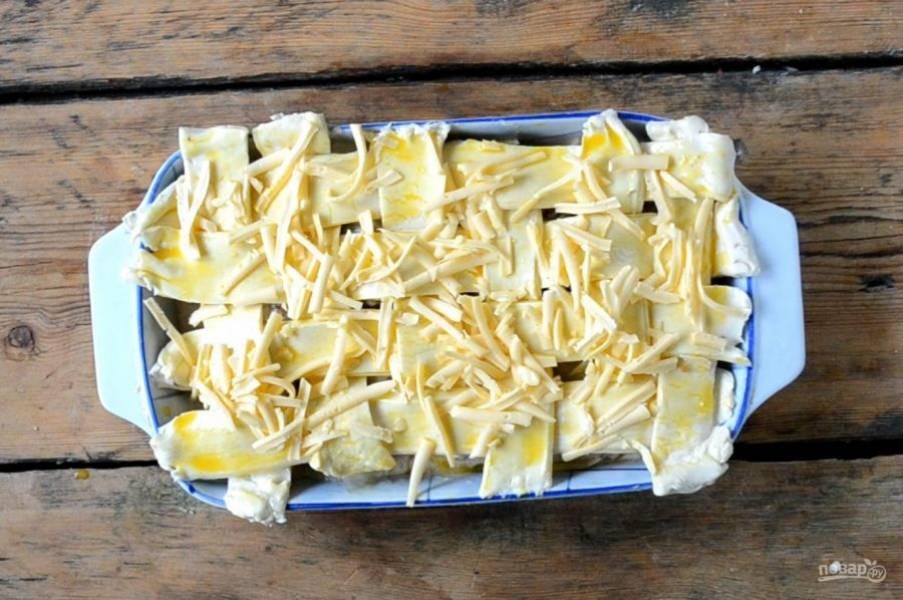 Слоеное тесто смажьте взбитым яйцом и присыпьте натертым твердым сыром. Отправьте в духовку и запекайте при 180 градусах 20 минут. Сверху пирог должен стать золотистым.
