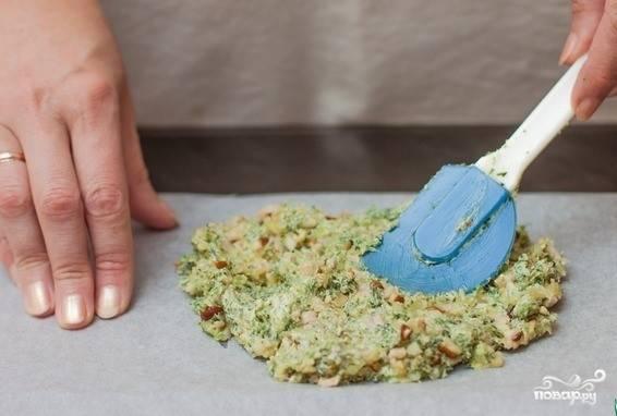 2. Постелите лист бумаги для выпечки. Выложите на него ароматное масло, разровняйте. Сверху накройте вторым листом пергаментной бумаги. Возьмите скалку, раскатайте весь кусок, чтобы равномерно распределилась толщина (3-4 мм). После чего уберите в морозилку.