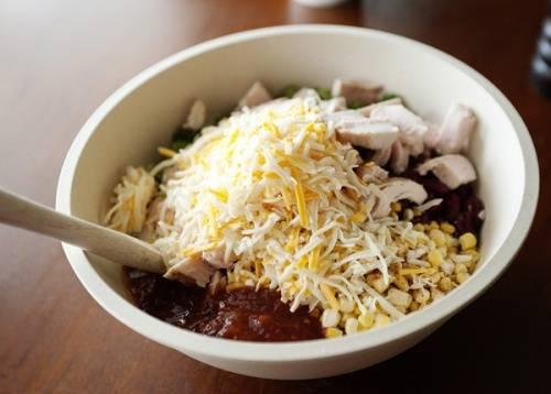 Теперь в чашку высыпаем фасоль, кукурузу, но без воды, при желании, можно добавить несколько ложек рассола. Не забываем туда вылить стакана соуса и добавить половину сыра. К ним выкладываем рис, курицу, солим, перчим, посыпаем орегано и перемешиваем.