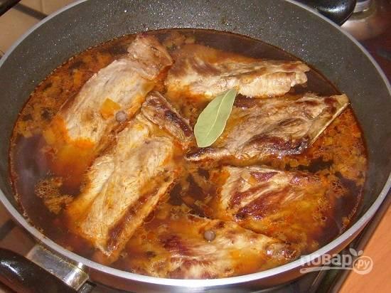 Наливаем в сковороду стакан воды, размешиваем содержимое и добавим оставшиеся специи. Выложим ребрышки. Накрываем крышкой и тушим на небольшом огне до готовности мяса.