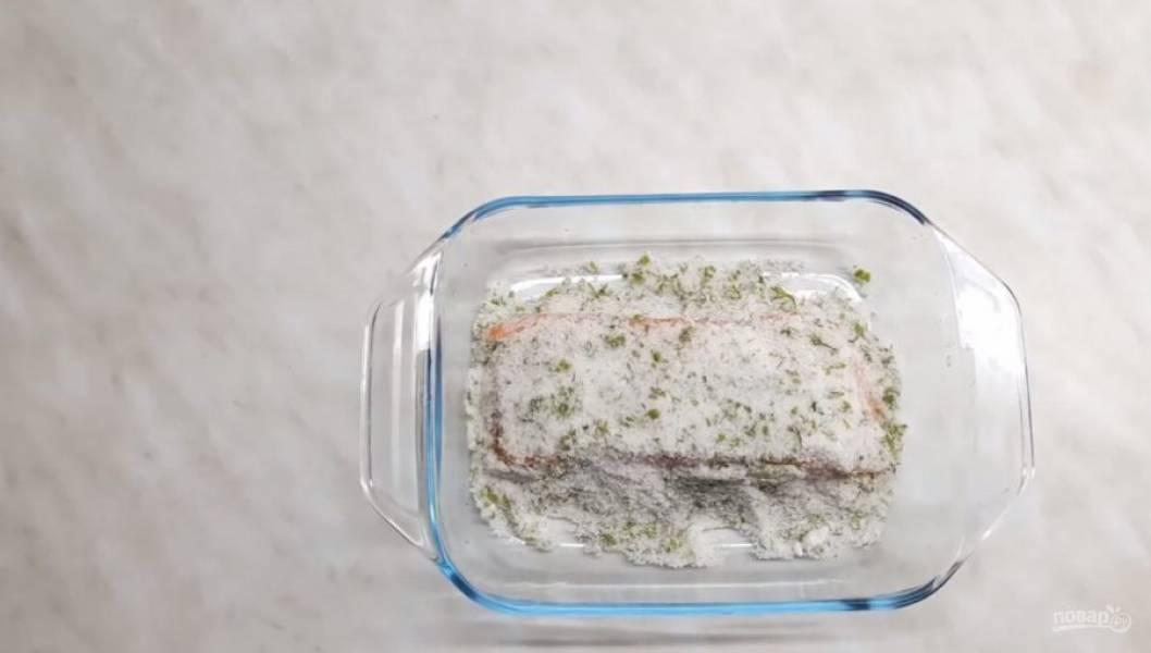 2. Выложите немного этой смеси на дно формы, в которой вы будете солить рыбу. Сверху выложите очищенную от чешуи рыбу и аккуратно обсыпьте её солью со всех сторон.