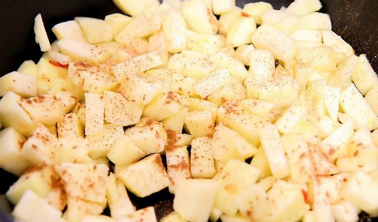 Для начала нужно испечь блинчики (об этом ниже). Займемся начинкой. Яблоки очистите от кожуры и нарежьте мелкими кубиками. Высыпаем яблоки на сковороду, присыпаем сахаром и корицей.
