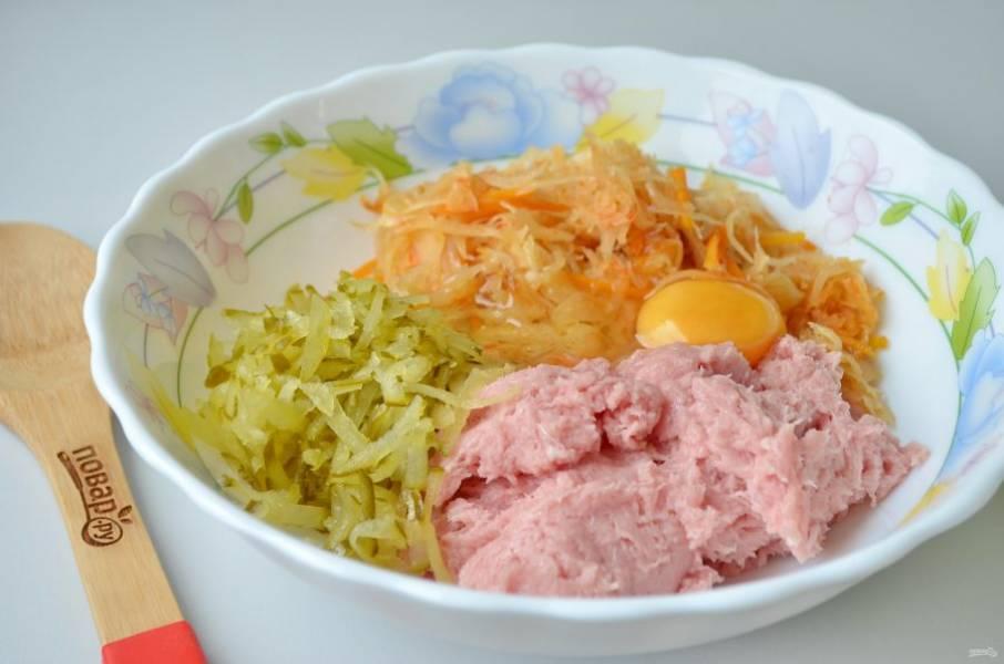 2. Кусочек свинины пропустите через мясорубку или измельчите другим удобным способом. Добавьте к нему тушеную капусту, тертые соленые огурцы и сырое яйцо.