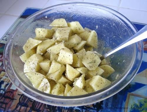 Заливаем в миску с картошкой растительного масла, добавляем специй, соли и перемешиваем.