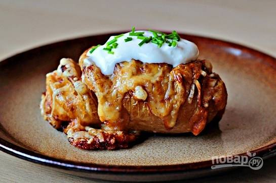 Подавайте картошку горячей, положив сверху ложечку сметаны и свежую зелень.