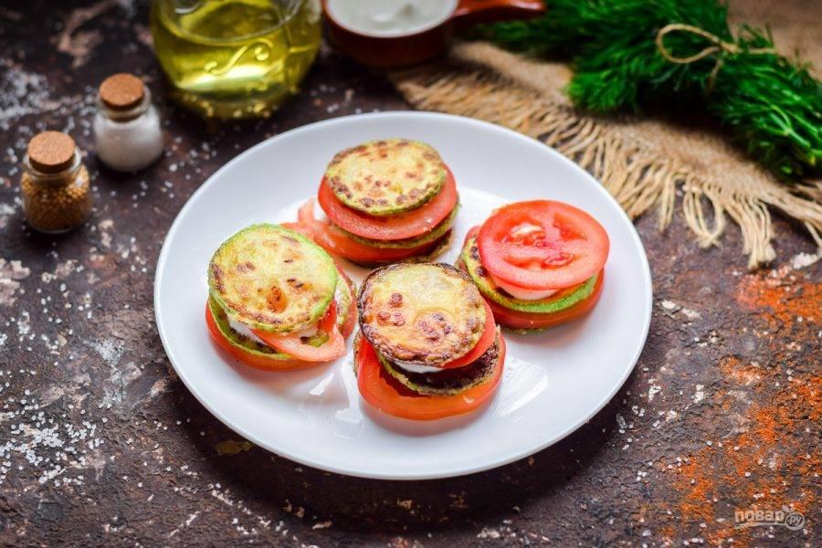 Помидоры нарежьте кружочками. Сложите закуску следующим образом - выложите кабачки, поверх немного сметаны или майонеза, соль, перец, чеснок и кружочек помидора. Сделайте несколько слоев.