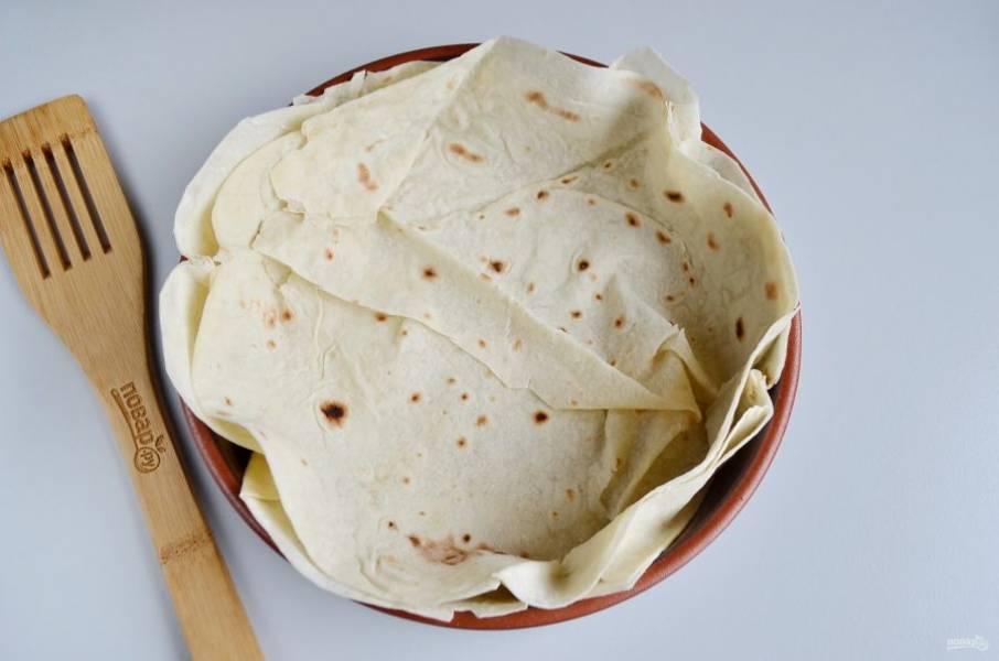 Возьмите один большой лаваш, кулинарными ножницами вырежьте круг (по диаметру больше формы для выпечки), чтобы получилась тарелочка. У меня остался хороший кусочек лаваша, я сделала второй слой, таким образом и пирог будет прочнее, и лаваш не пропадет. Смажьте лаваш растительным маслом.