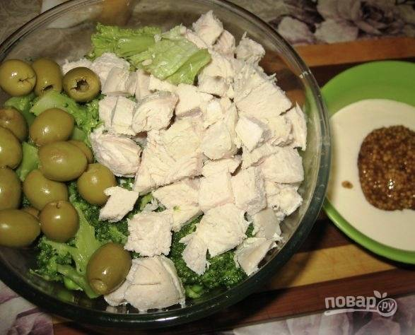 Теперь вернемся к остывшей курочке. Нарежем её небольшого размера кубиками. Салатные листья промоем, обсушим и порвем руками на любого размера кусочки. К курочке с салатом теперь переложим горошек и брокколи, а также оливки (жидкость, в которой они находились, нужно предварительно слить). Все ингредиенты посолите, можете добавить любимые специи. В отдельной небольшой ёмкости сделаем заправку для салата: для этого смешиваем сметану и горчицу.