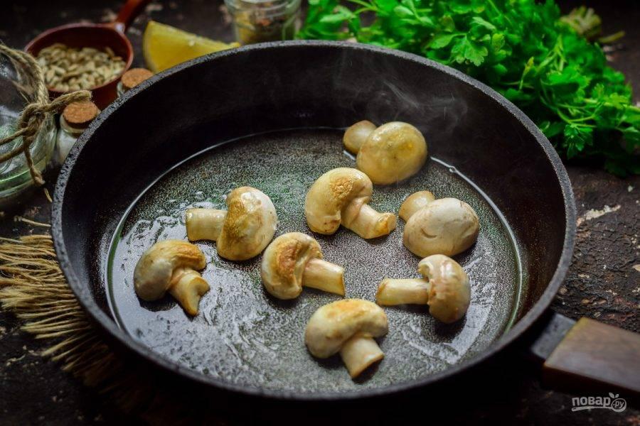 Прогрейте сковороду, слегка смажьте маслом и выложите грибы. Жарьте шампиньоны с обеих сторон по 2-3 минуты.