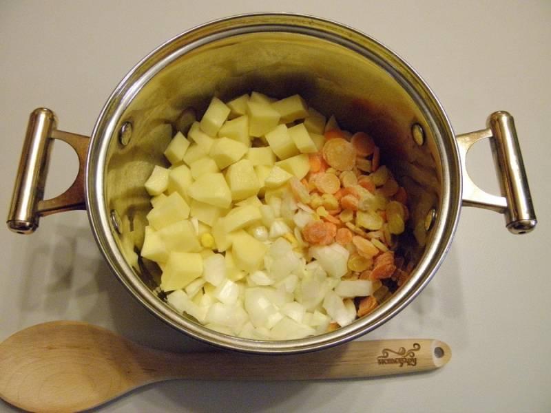 Тщательно промойте овощи. Картофель, лук и морковь нарезаем мелкими кубиками и помещаем в кастрюлю. Заливаем водой и ставим вариться.