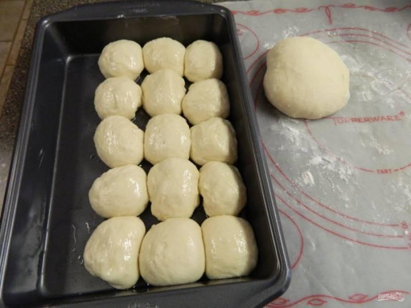 Тесто делим на одинаковые комочки, форму для выпечки смазываем растительным маслом и начинаем формировать булочки, выкладываем их в форму.