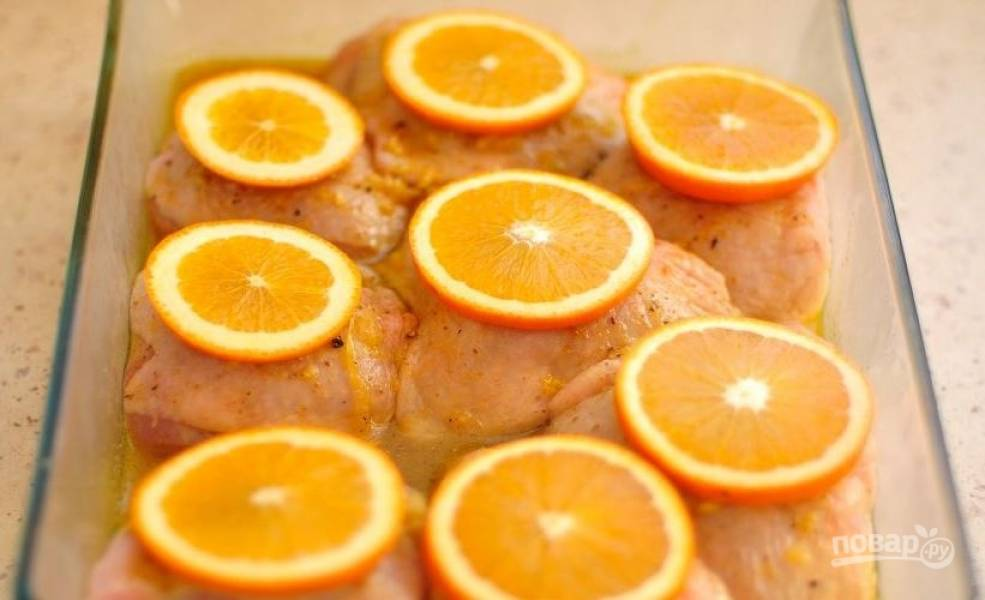 Замаринованную курицу достаньте из холодильника. Апельсин вымойте, обсушите и нарежьте колечками около сантиметра шириной. Выложите по одному кружочку апельсина на каждый кусочек курицы.