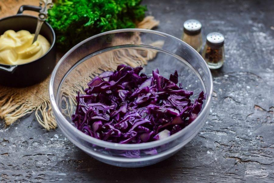 Красную капусту сполосните и просушите, после нарежьте тонкой полоской. Выложите капусту в салатник.