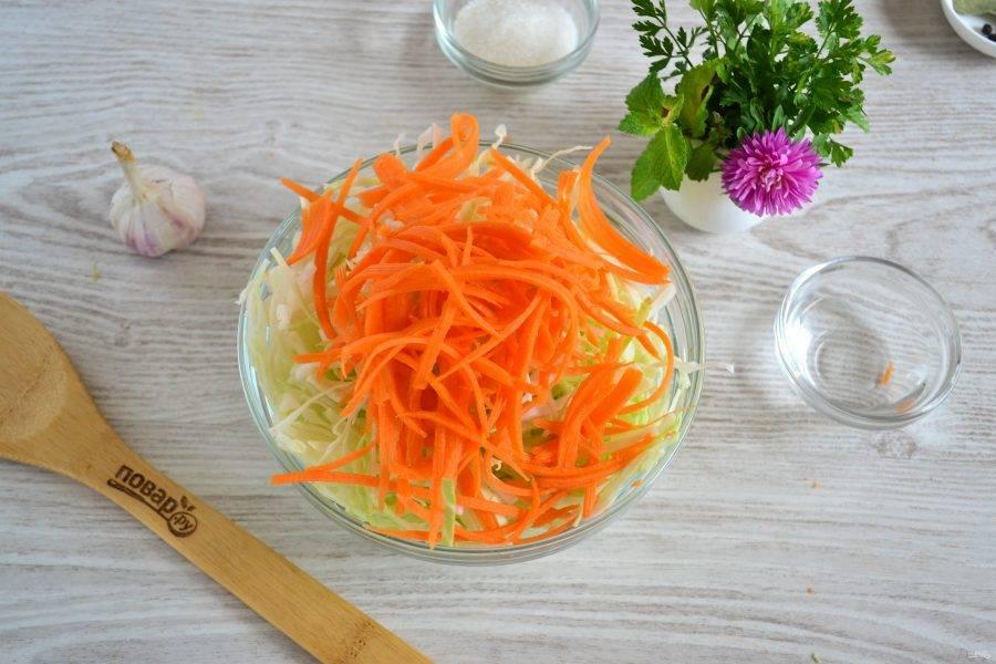 Морковь натрите на крупной терке. Мне нравится натирать на терке для моркови по-корейски, так ее лучше видно в готовом салате и, как мне кажется, она получается вкуснее. Добавьте морковь к капусте.