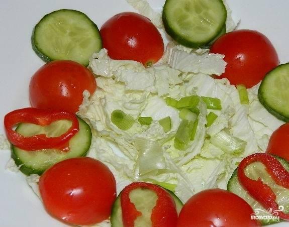 5.Огурец порежьте кружочками, а помидоры — на две части. Накрошите зеленый лук или зелень. Все это красиво уложите сверху капусты.