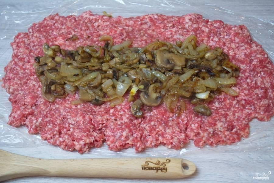 По центру мясного пласта выложите обжаренные с луком грибы.