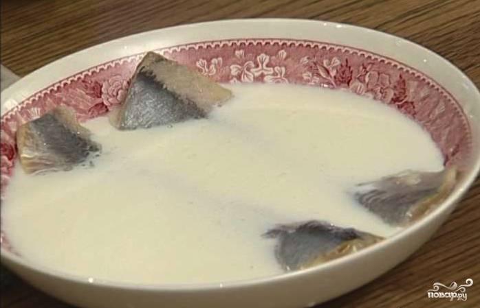 Филе сельди проверяем на наличие косточек, при обнаружении удаляем их. Укладываем рыбу в тарелку, заливаем молоком. Даём постоять около 30 минут.