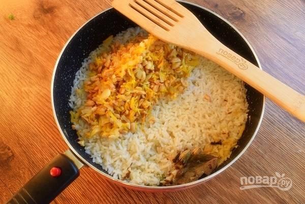 Добавьте жареные овощи и арахис в пряный рис, перемешайте.