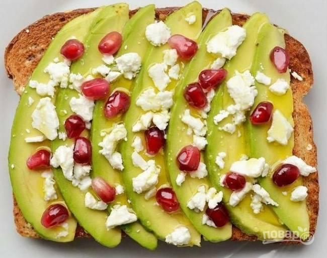 Для начала приготовьте тосты, поджарив их привычным для вас способом. На первый кусок нарежьте ломтики авокадо. Рассыпьте немного сыра и разложите зернышки граната. Сверху добавьте масло.