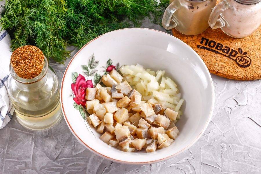 Очистите репчатый лук и промойте в воде, нарежьте мелкими кубиками. Всыпьте в пиалу и залейте уксусом, оставляя на 5 минут, чтобы нарезка промариновалась и из нее ушла горечь. Слабосоленое филе сельди нарежьте мелкими кубиками и добавьте в глубокую емкость. Туда же выложите маринованный лук, стряхнув лишнюю жидкость.