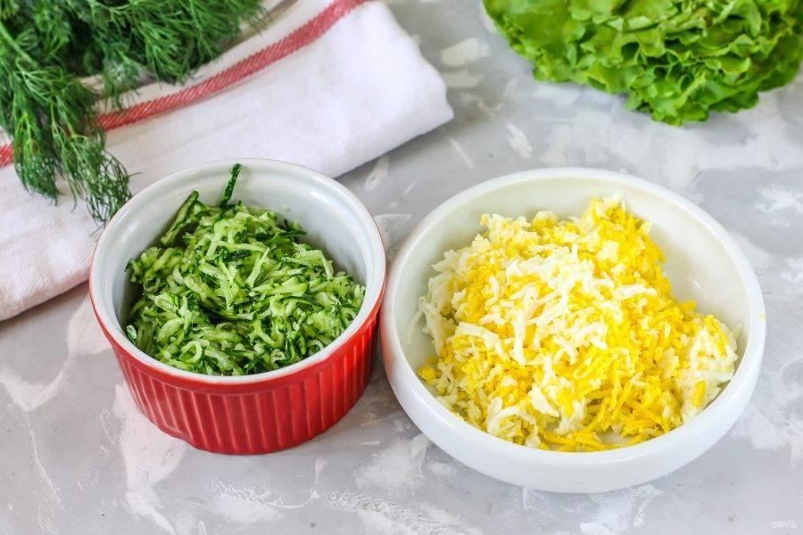Огурцы промойте в воде и срежьте хвостики с обеих сторон овощей. Натрите их на терке в пиалу и присолите, через 5 минут отожмите огуречную нарезку от выделенного сока. Куриные яйца очистите, промойте в воде и также натрите на терке. Присолите.