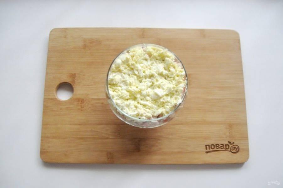 Яйца сварите вкрутую, охладите, очистите и натрите на терке. Выложите следующим слоем салата, смажьте майонезом.