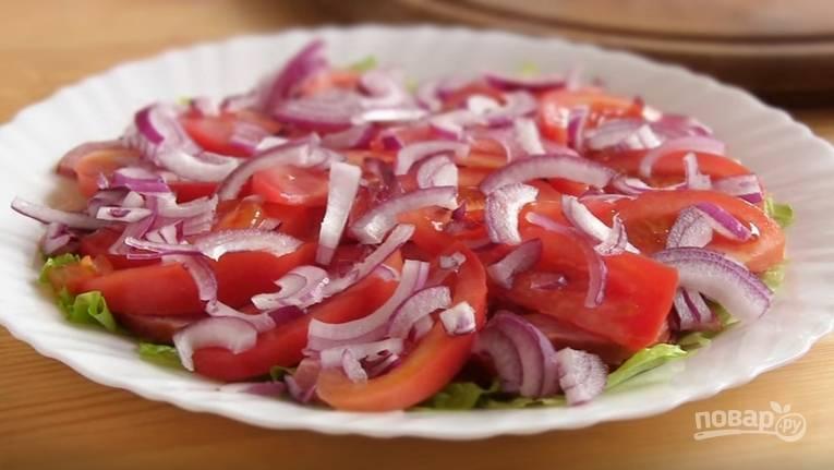 3. Помидоры нарежьте дольками, а лук — полукольцами. Переложите их сверху на колбасу.