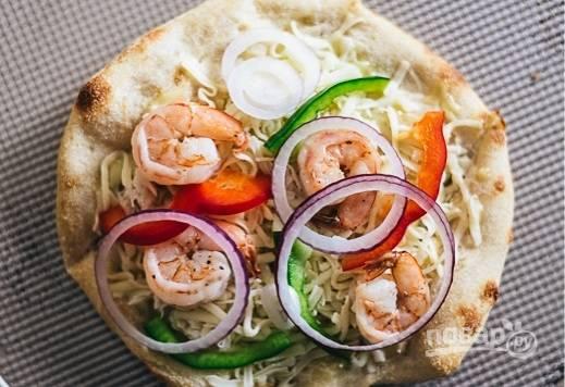 3. На корж выложите соус и немного сыра, креветки, рыбку, овощи, ананасы. Присыпьте все сверху тертым сыром. Отправьте запекаться минут на 8 в духовку.