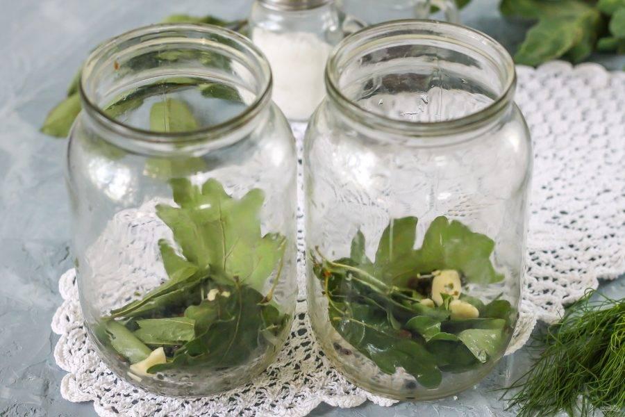 Промойте банки. Промойте и листья дуба, хрена, вишни, смородины - подойдут любые из них. Листья дуба и хрена обладают дубильными веществами - благодаря им огурчики останутся хрустящими. Выложите листья в банки вместе с промытым укропом или укропными зонтиками. Очистите зубчики чеснока, добавьте их в банки вместе с горошинами черного перца.