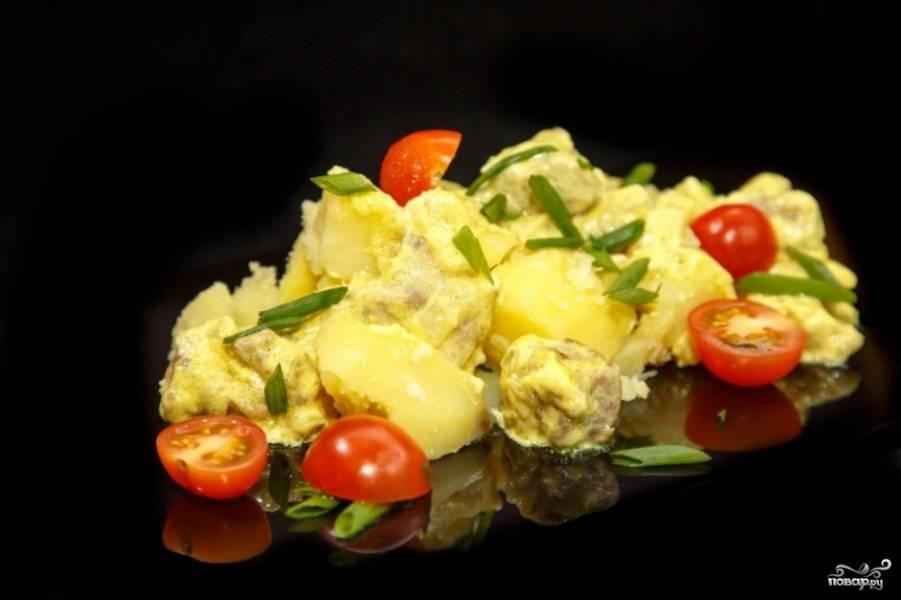 С отваренного картофеля слейте воду, добавьте его в сковороду и перемешайте с соусом. Вымойте и нарежьте помидоры черри, нарежьте зелёный лук. Выложите на блюдо картофель с луком, а затем положите помидоры и лук.