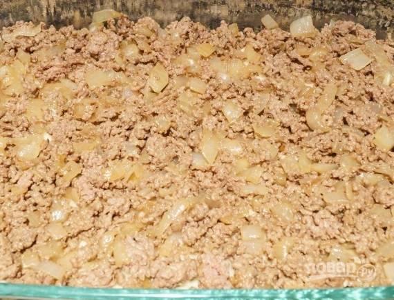 2. На сковороде с небольшим количеством масла обжарьте измельченный лук до прозрачности. Выложите фарш и жарьте на среднем огне до готовности. Посолите и поперчите по вкусу, выложите на картофель в форму.