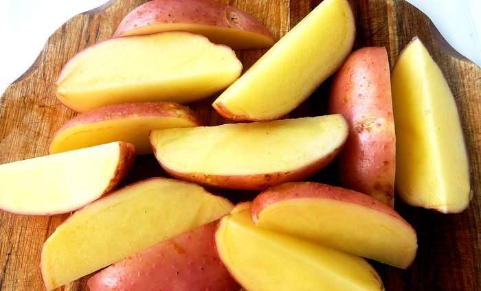 Молодой картофель тщательно промывается и зачищается щеточкой (не чистится). Затем режем его на 4 части дольками.