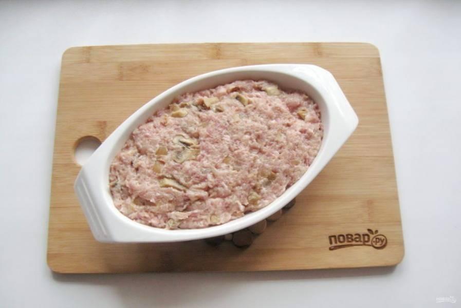 Форму для запекания мясного хлеба смажьте маслом и выложите приготовленный фарш.