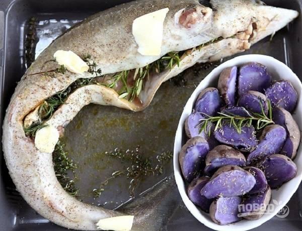 На следующий день оставшееся масло выложим кусочками на рыбу, на противень наливаем вино, выкладываем разрезанную головку чеснока и веточки розмарина и тимьяна. На свободное место можно поставить запекаться картофель. На фото фиолетовый картофель.
