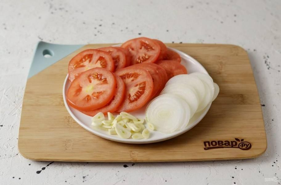 Нарежьте помидоры и репчатый лук кружочками. Чеснок очистите, нарежьте пластинами.