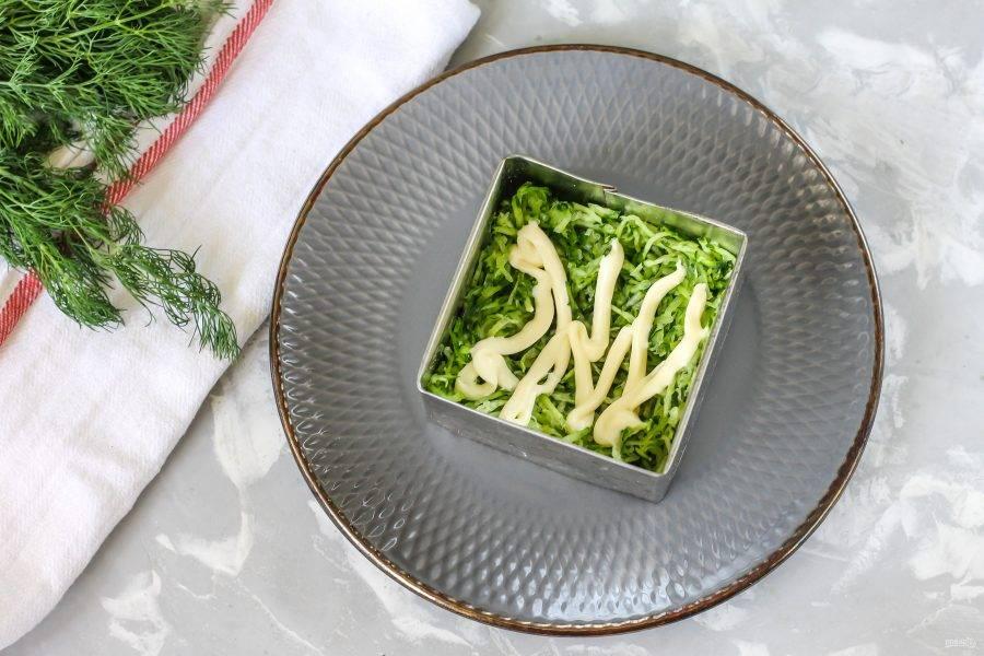 В кулинарное кольцо или в квадрат выложите огуречную нарезку, слегка прижмите ее и нарисуйте сверху майонезную сеточку. Сметану в таких блюдах лучше не использовать, так как она расслаивается и салат может поплыть.