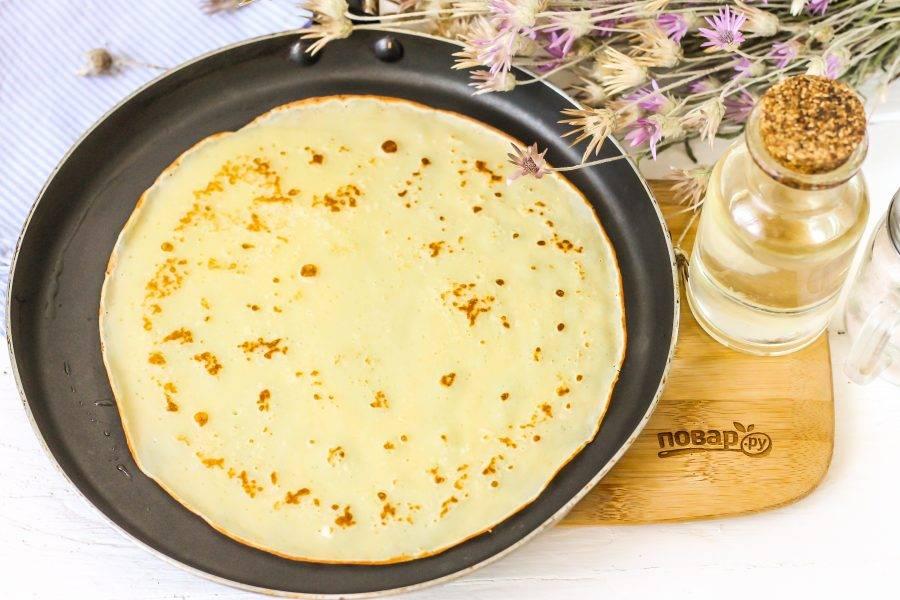 Разогрейте сковороду и смажьте ее в первый раз растительным маслом. Влейте порцию теста и испеките блин по минуте с каждой стороны до румяности.