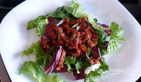 Откройте банку с вялеными томатами. Порежьте помидоры на тонкие полоски и выложите их на листья салата в тарелку.
