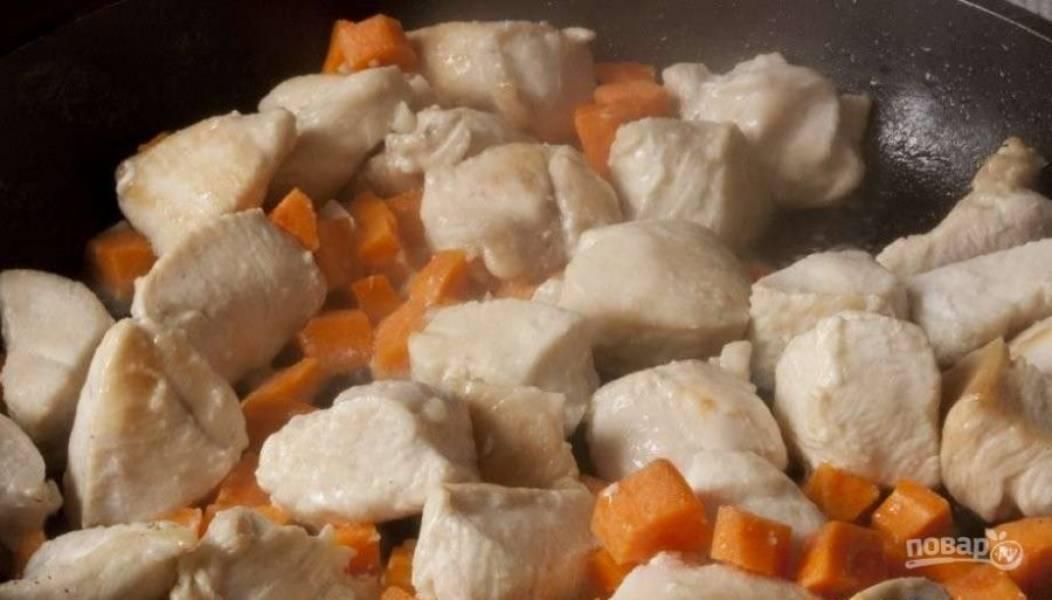 Морковь почистите и некрупно нарежьте. Чеснок измельчите. Добавьте эти овощи к курице. Перемешайте ингредиенты, и жарьте их на среднем огне.