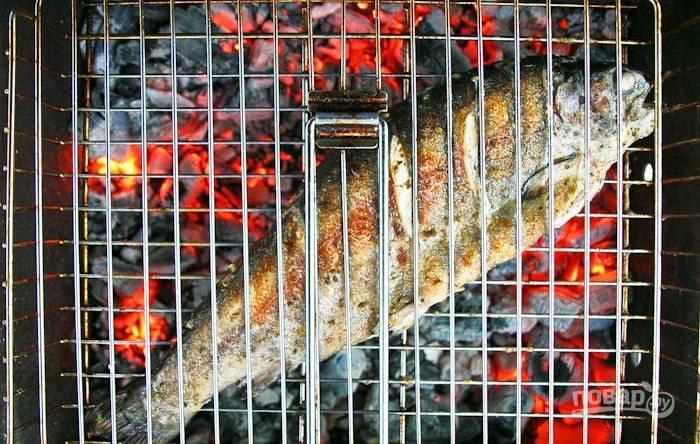 4.Разогреваю угли и выкладываю на решетку рыбку, закрываю решетку-гриль и отправляю на тлеющие угли. Обжариваю рыбку с двух сторон до золотистой корочки.