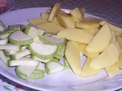 1. Подготовим ингредиенты. Мясо размораживаем и делим на кусочки на 2-3 ребра. Лук и морковку измельчаем, а картофель с кабачком режем средними ломтиками.