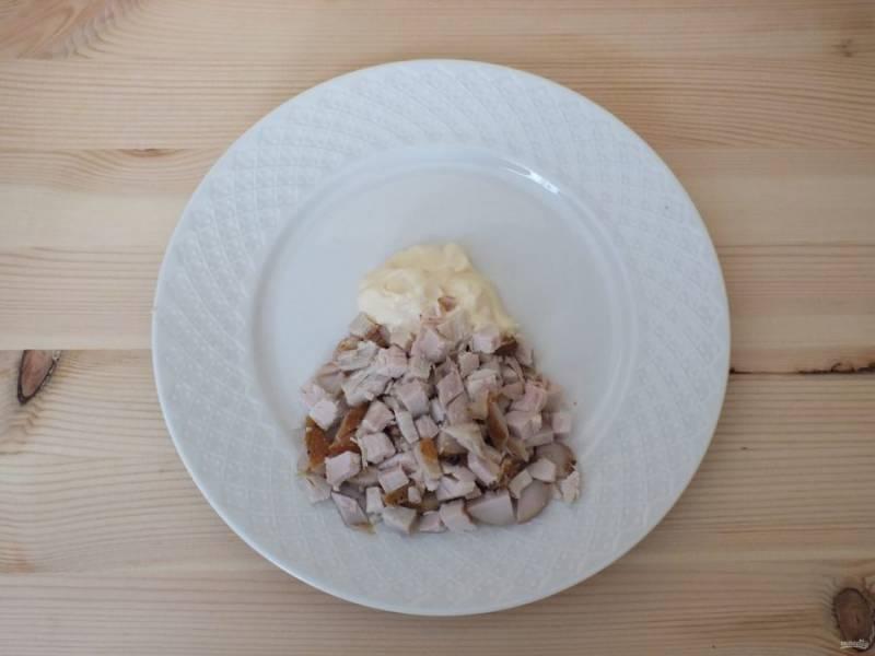 Возьмите плоское блюдо. В середину блюда выложите майонез, около 1,5-2 ст. л. Куриное филе нарежьте кубиком и положите сектором на тарелку.
